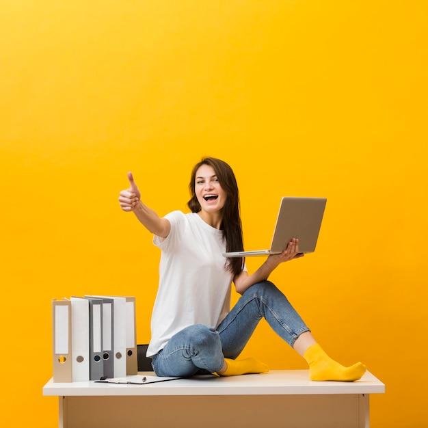 Vista lateral da mulher sorridente, sentado na mesa e dando polegares para cima enquanto segura o laptop