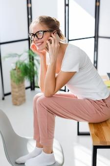 Vista lateral da mulher sorridente, trabalhando em casa enquanto no telefone