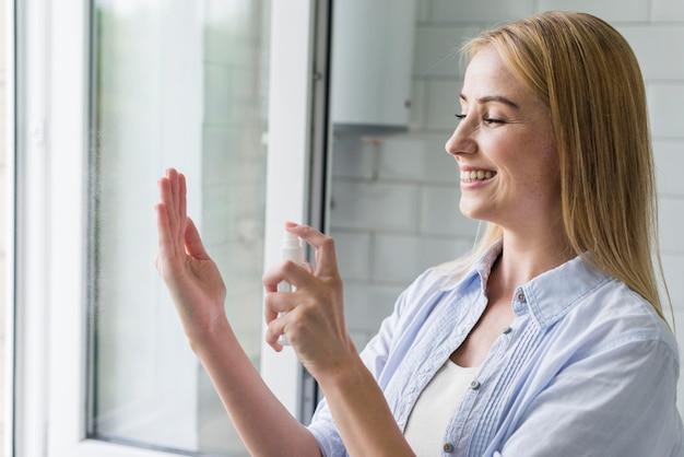 Vista lateral da mulher sorridente usando desinfetante para as mãos