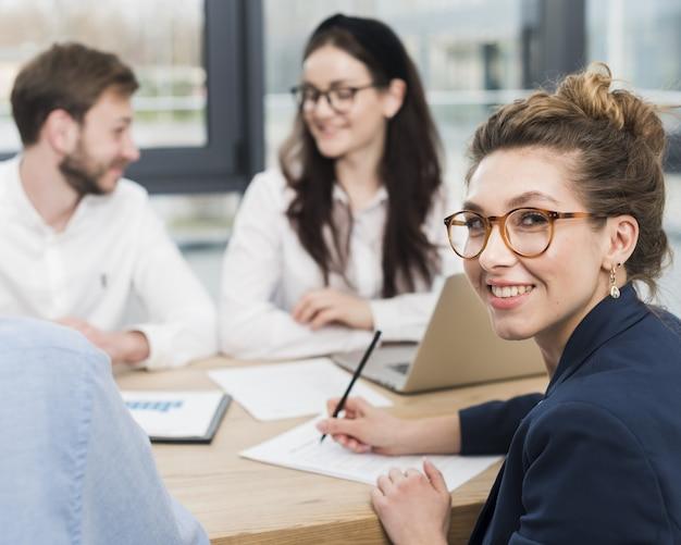Vista lateral da mulher sorrindo enquanto assina contrato de trabalho