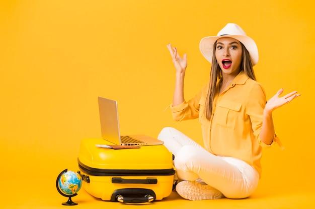 Vista lateral da mulher surpreendida usando um chapéu enquanto posava ao lado de bagagem