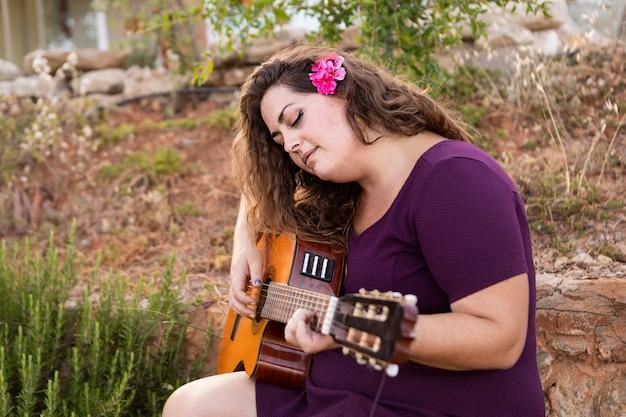 Vista lateral da mulher tocando violão com flor no cabelo