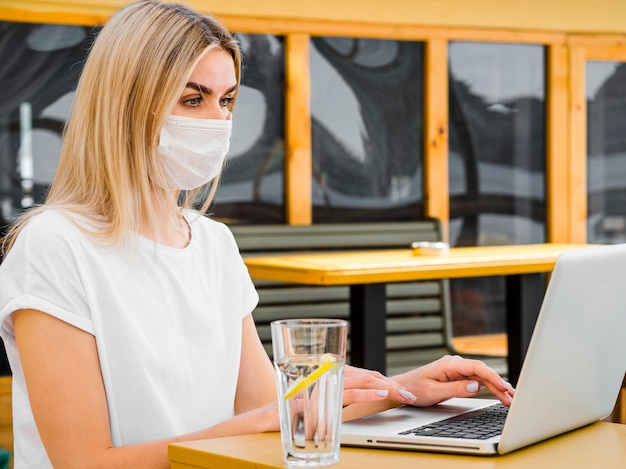 Vista lateral da mulher tomando um copo de água e trabalhando no laptop
