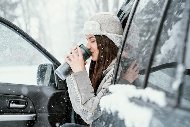 Vista lateral da mulher tomando uma bebida quente e curtindo a neve durante uma viagem