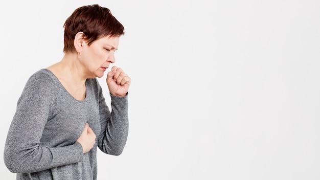 Vista lateral da mulher tossindo