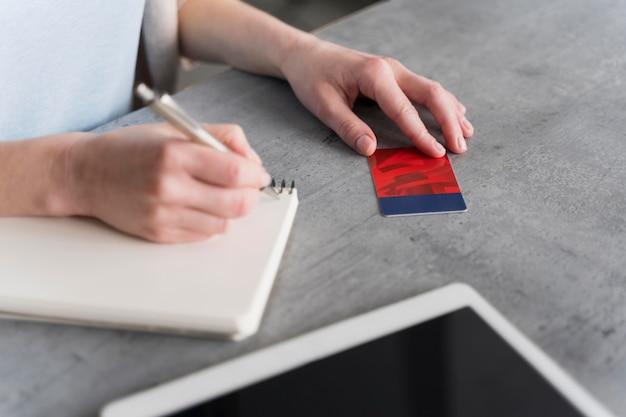 Vista lateral da mulher trabalhando e escrevendo no caderno