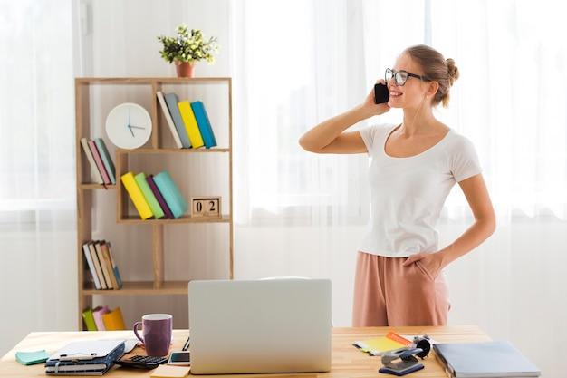 Vista lateral da mulher trabalhando em casa e falando no telefone