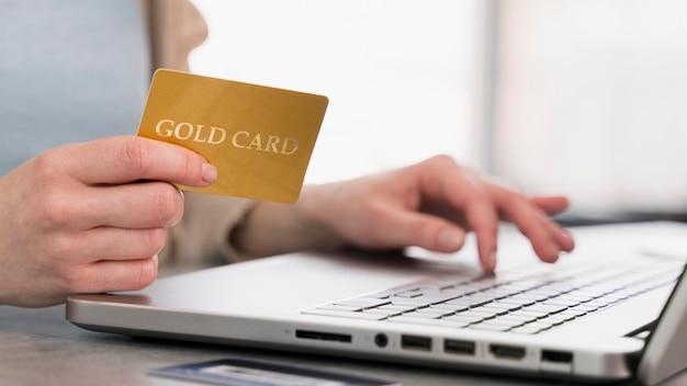 Vista lateral da mulher trabalhando no laptop e segurando o cartão de crédito