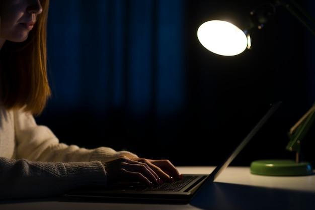 Vista lateral da mulher trabalhando no laptop