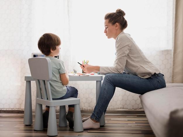 Vista lateral da mulher tutoria criança em casa
