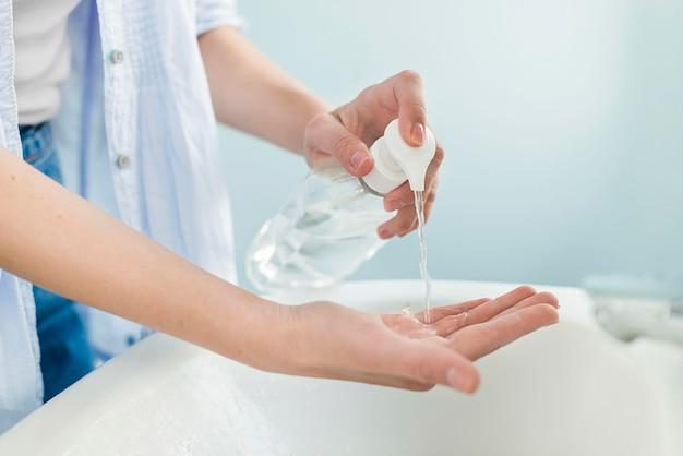 Vista lateral da mulher usando sabonete líquido