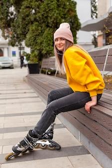 Vista lateral da mulher vestindo gorro e patins