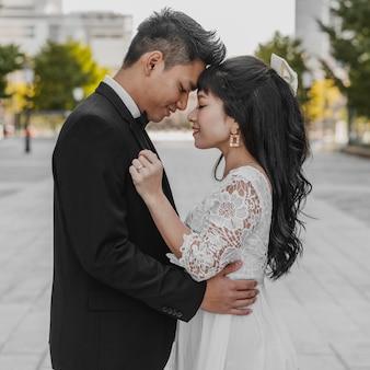 Vista lateral da noiva e do noivo abraçados na rua