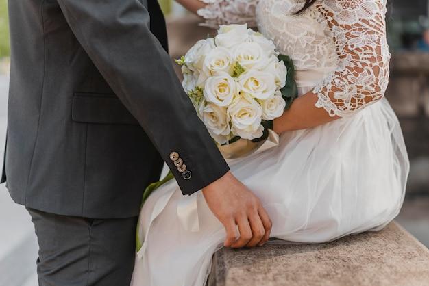 Vista lateral da noiva e do noivo com buquê de flores