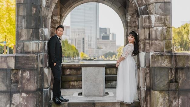 Vista lateral da noiva e do noivo posando contra a parede