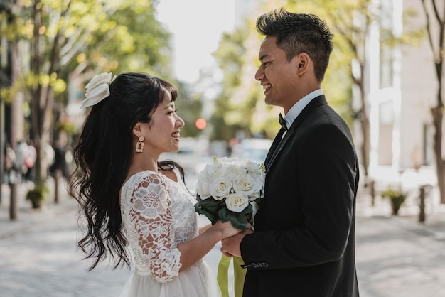 Vista lateral da noiva e do noivo posando na rua