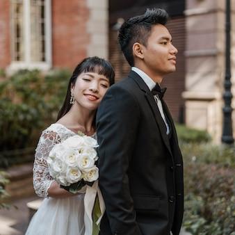 Vista lateral da noiva em pé atrás do noivo, segurando o buquê