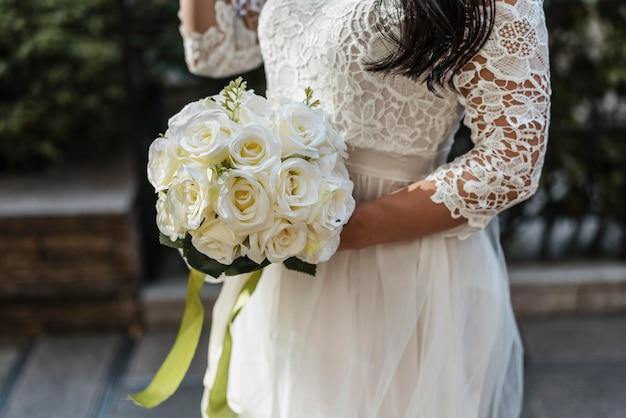 Vista lateral da noiva segurando um buquê de flores