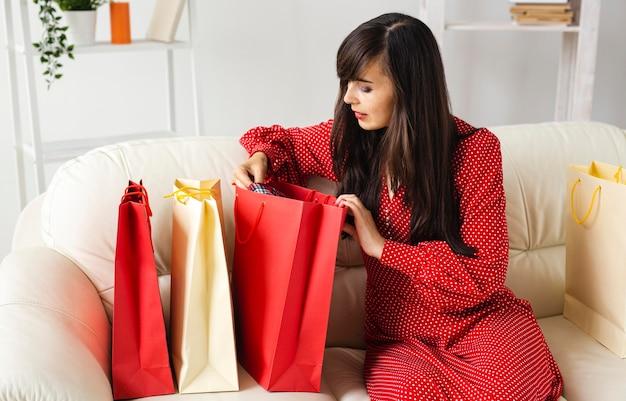 Vista lateral da owoman verificando os itens que ela recebeu enquanto fazia compras em promoção