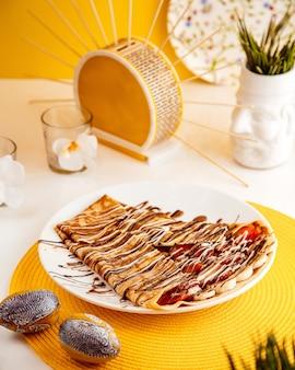 Vista lateral da panqueca fina com morangos fatiados e bananas cobertas com calda de chocolate no prato branco