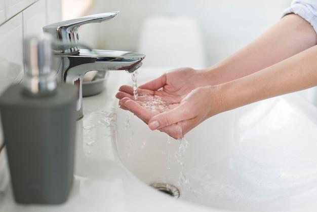 Vista lateral da pessoa lavando as mãos antes de lavar com sabão