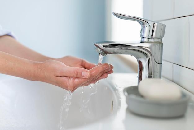 Vista lateral da pessoa lavando as mãos com água