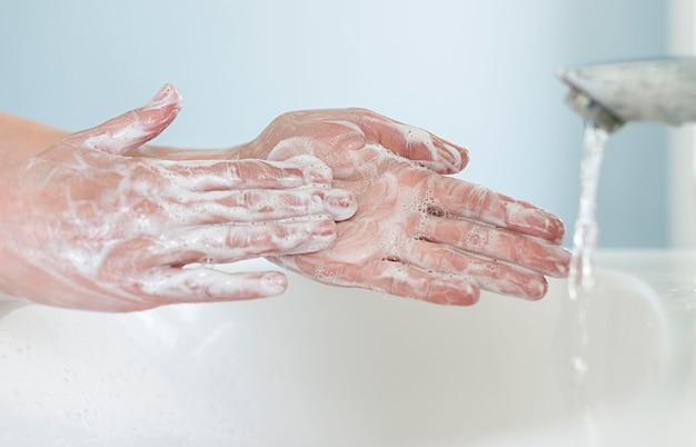 Vista lateral da pessoa lavando as mãos com sabão