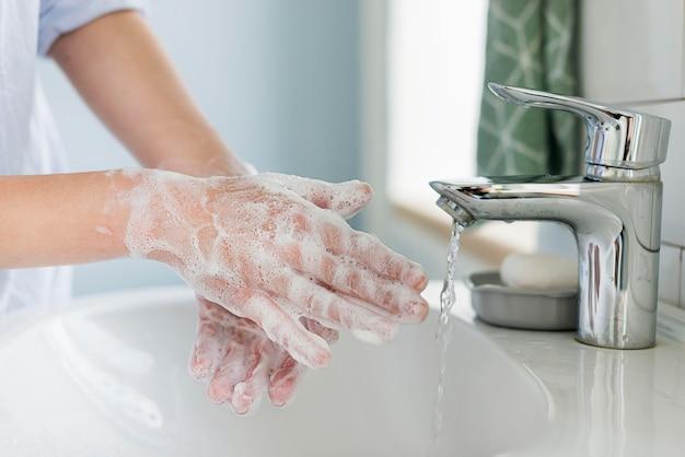 Vista lateral da pessoa lavando as mãos na pia