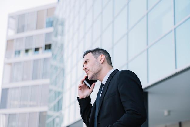 Vista lateral da pessoa que faz negócios telefonando