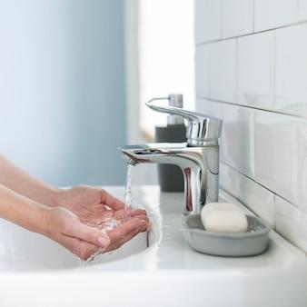 Vista lateral da pessoa se preparando para lavar as mãos na pia