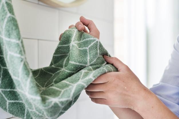 Vista lateral da pessoa secando as mãos usando toalha