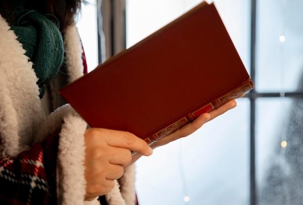 Vista lateral da pessoa segurando um livro aberto