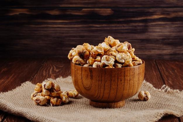 Vista lateral da pipoca de caramelo doce em uma tigela de madeira no fundo rústico