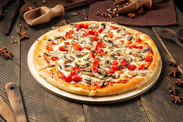 Vista lateral da pizza com cogumelos e tomate na mesa de madeira