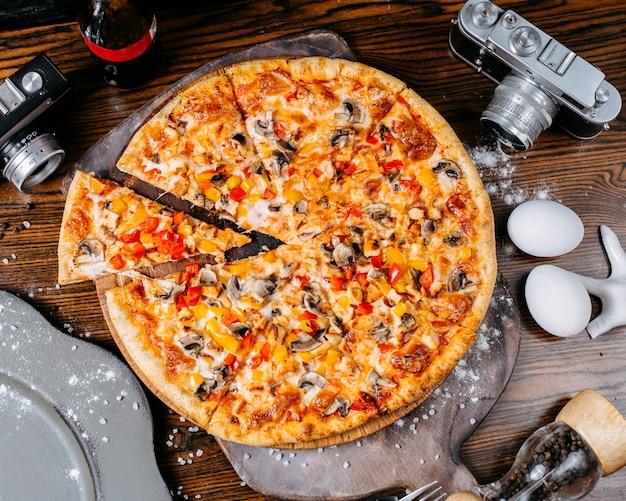 Vista lateral da pizza com cogumelos pimentões coloridos