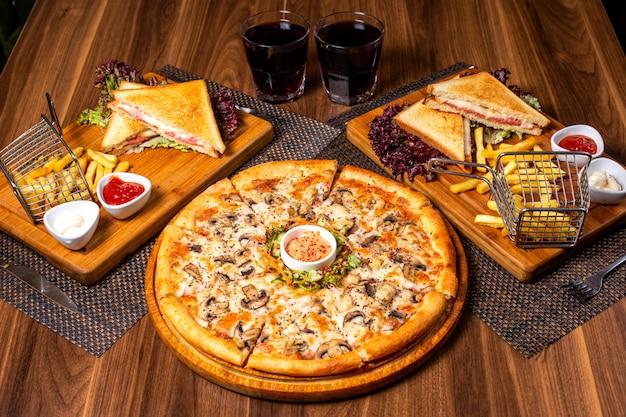 Vista lateral da pizza com frango e cogumelos, servido com salada de legumes e molho na chapa de madeira