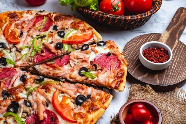 Vista lateral da pizza com salame presunto pimentão verde tomate azeitonas pretas e queijo em cima da mesa