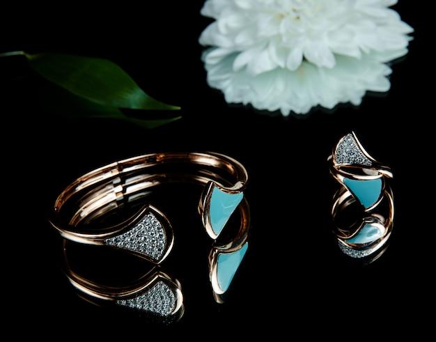 Vista lateral da pulseira e anel banhados a ouro com cristal e esmalte na mesa preta