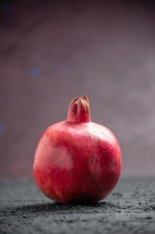 Vista lateral da romã vermelha romã vermelha madura na mesa cinza sobre fundo roxo