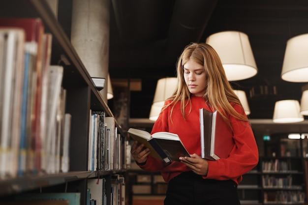Vista lateral da ruiva esperta na biblioteca, em pé perto das prateleiras e lendo um livro focado.