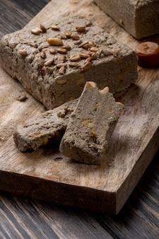 Vista lateral da saborosa halva com sementes de girassol em uma placa de madeira