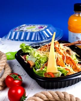 Vista lateral da salada caesar com frango e queijo na caixa de entrega