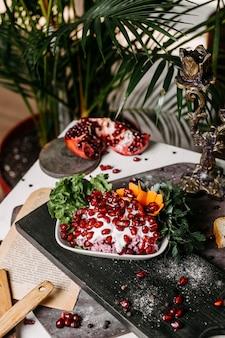 Vista lateral da salada de beterraba com molho de maionese e romã em uma placa de madeira
