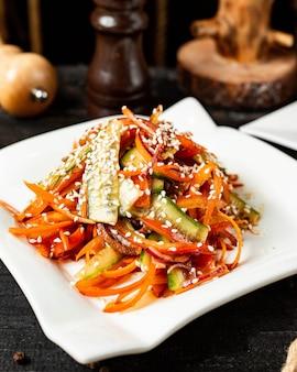 Vista lateral da salada de cenoura com pepino pimentão e gergelim no prato
