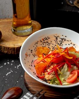 Vista lateral da salada de frango com pimentões coloridos tomates batatas fritas e sementes de cominho em uma tigela em cima da mesa
