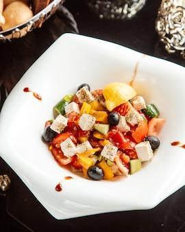 Vista lateral da salada de legumes com queijo feta e azeitonas em um prato branco