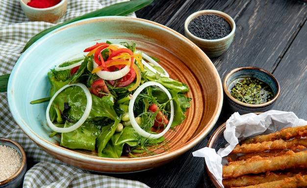 Vista lateral da salada de legumes fresca em um prato servido com molho de soja e sementes pretas na mesa de madeira