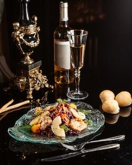 Vista lateral da salada de legumes picada com frango e abacaxi em um prato na mesa