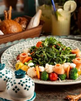 Vista lateral da salada de salmão defumado com legumes e rúcula em um prato na mesa