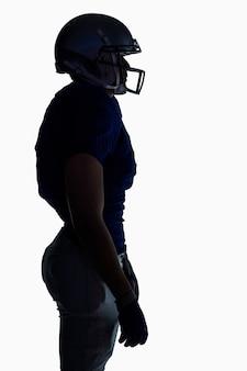 Vista lateral da silhueta jogador de futebol americano de pé